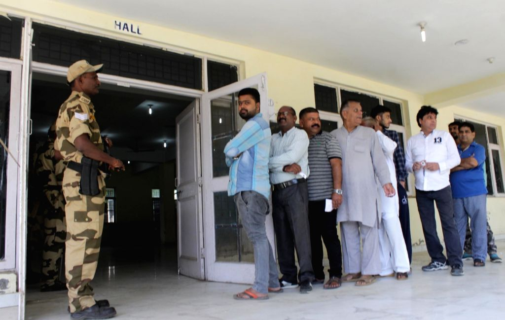 Voters wait in a queue to cast their votes amid tight security at a polling center during the Jammu and Kashmir municipal polls. (File Photo: IANS)