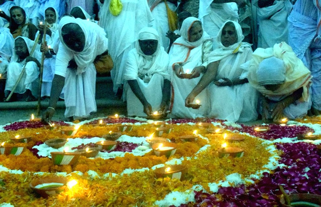 Vrindavan widows light earthen lamps placed around a 'rangoli' as they participate in Diwali celebrations ahead of the festival, at Kesi Ghat in Vrindavan of Uttar Pradesh's Mathura district ...