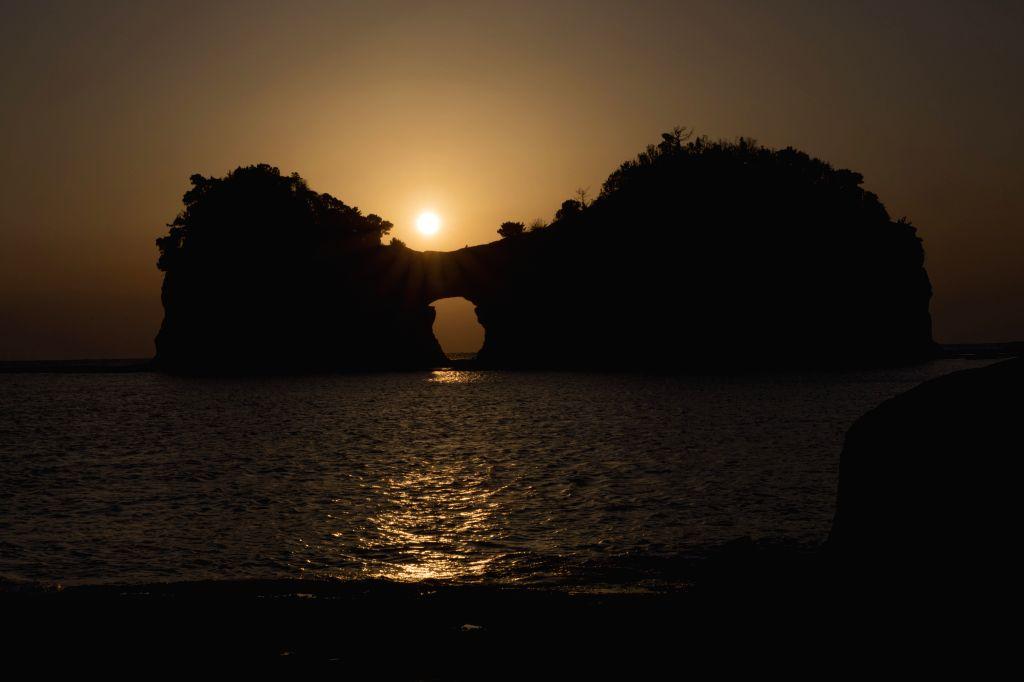 WAKAYAMA, Feb. 13, 2019 - Photo taken on Feb. 13, 2019 shows Engetsu Island under sunset in Wakayama, Japan. Engetsu Island is a small island with a natural arch off the coast of Shirahama in Japan's ...