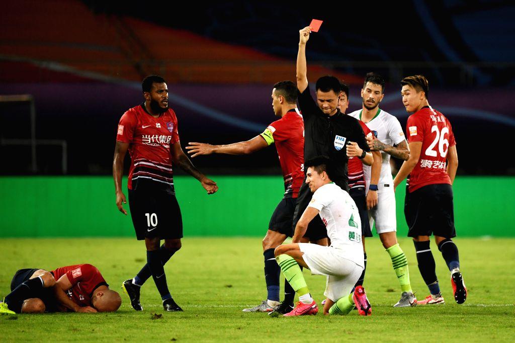 Wang Wei (below R) of Qingdao Huanghai gets a red card during the 4th round match between Chongqing Dangdai Lifan and Qingdao Huanghai at the postponed 2020 season ...