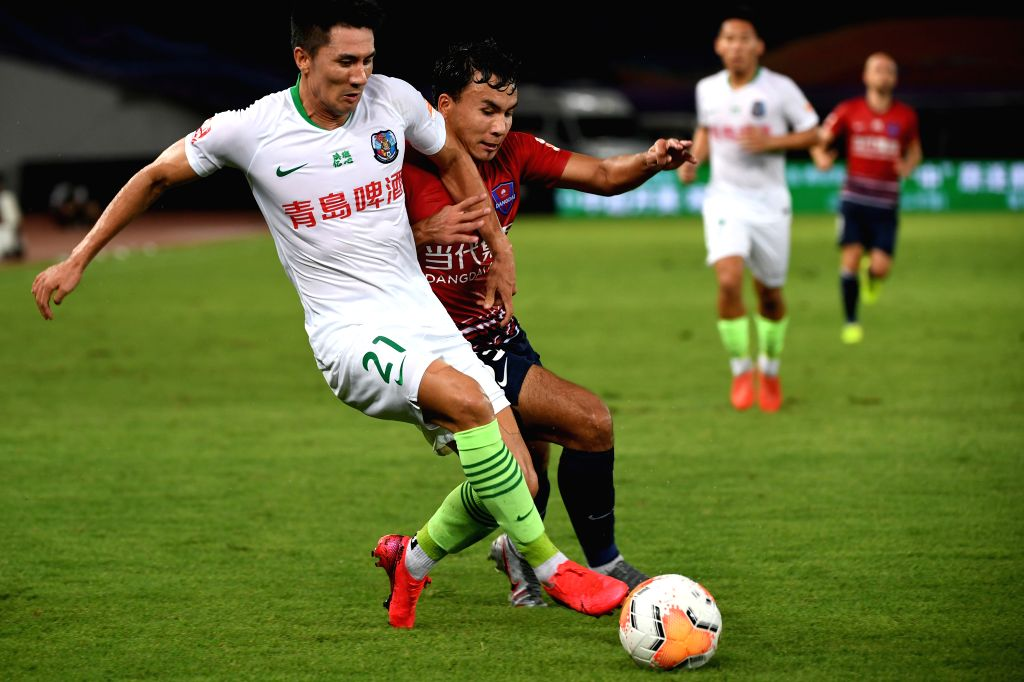 Wang Wei (L) of Qingdao Huanghai vies for the ball during the 4th round match between Chongqing Dangdai Lifan and Qingdao Huanghai at the postponed 2020 season ...