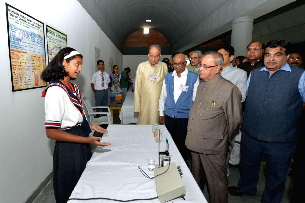 A student explains President Pranab Mukherjee her model displayed at an exhibition in Bajaj Science Centre of Wardha, Maharashta on Nov 26, 2014. Also seen the Union Road Transport, Highways . - Nitin Gadkari and Pranab Mukherjee