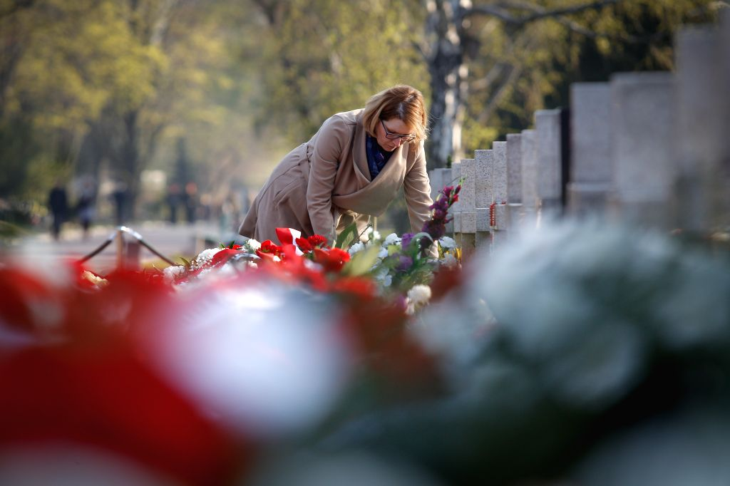 WARSAW, April 10, 2017 - A woman lays flowers to a tombstone at the Warsaw Powazki Military Cemetery in Warsaw, capital of Poland, April 10, 2017. Poland marked on Monday the seventh anniversary of ...