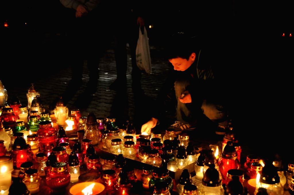 WARSAW, Nov. 1, 2018 - A boy lights a candle for the deceased at Powazkowski Cemetery in Warsaw, Poland, on Nov. 1, 2018. Millions of Polish people gathered at the cemeteries around the country to ...