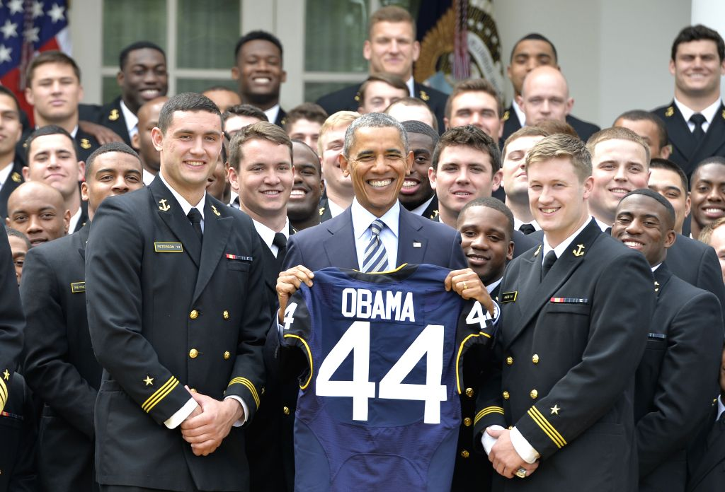 US President Barack Obama shows a gift jersey as he poses during the presentation of the Commander-in-Chief Trophy to the US Naval Academy Football Team at the .