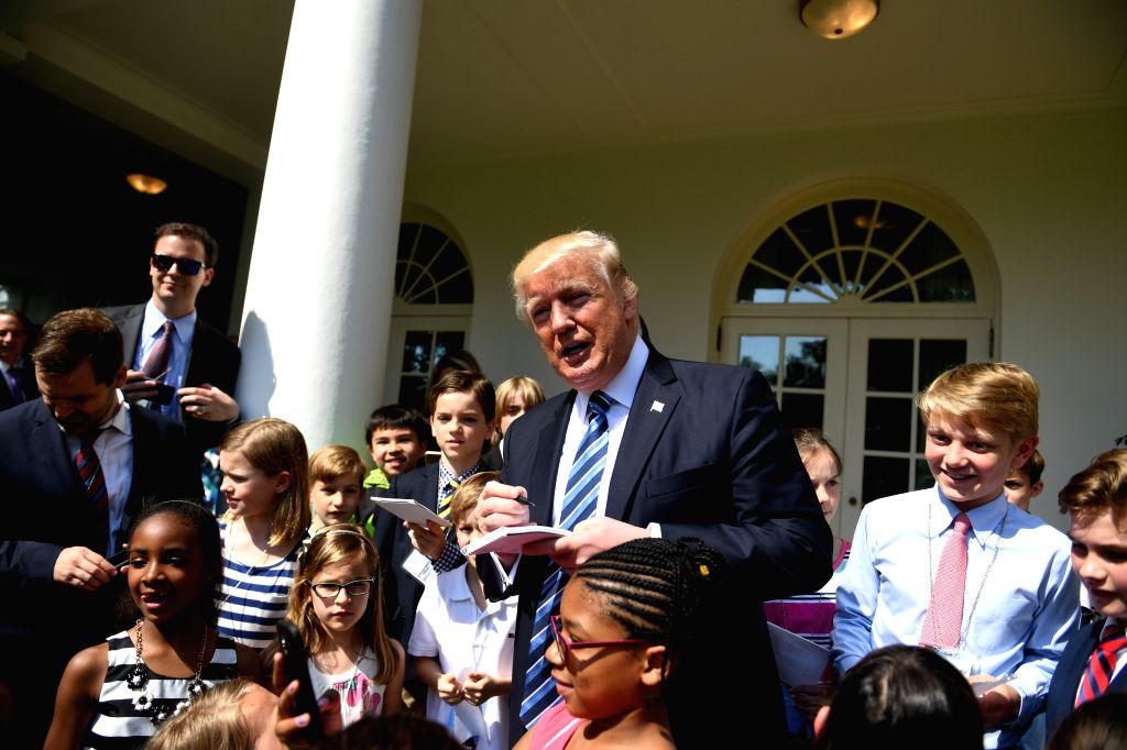 """WASHINGTON, April 27, 2017 - U.S. President Donald Trump (C) signs autographs for children of White House staffers and reporters during """"Take Our Daughters and Sons to Work Day"""" at the ..."""