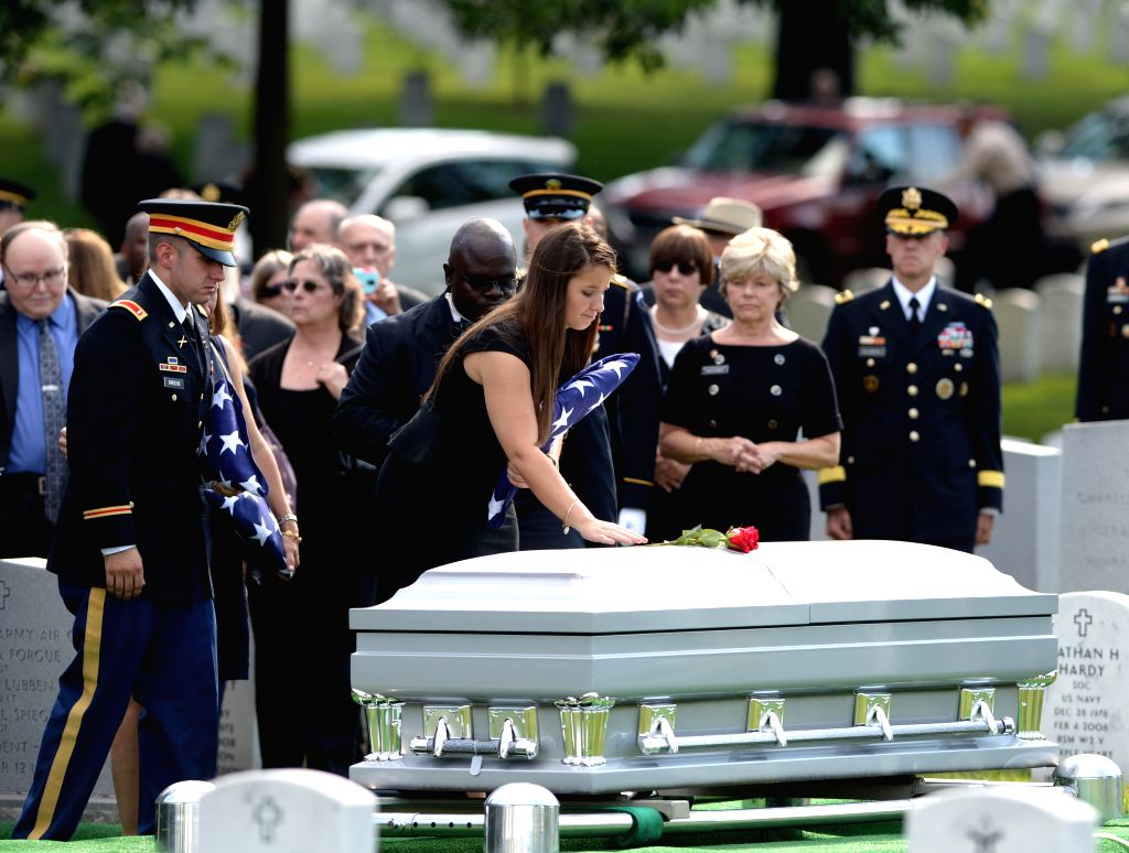 Amelia Greene presents a flower on the coffin of her father U.S. Army Maj. Gen. Harold Greene, during a burial service at section 60 of Arlington National ...