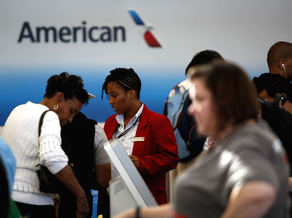 An American Airline staff helps passengers check in at Ronald Regan National Washington Airport in Washington D.C., the United States, on Aug. 15, 2015. ...