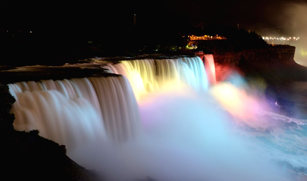 Niagara Falls is illuminated by colorful lights near the border between the United States and Canada on Aug. 16, 2014.