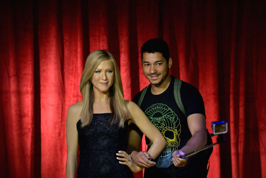 A visitor poses for photos with the wax figure of actress Jennifer Aniston at the Madame Tussauds in Washington D.C., the United States, Aug. 19, 2014. ...