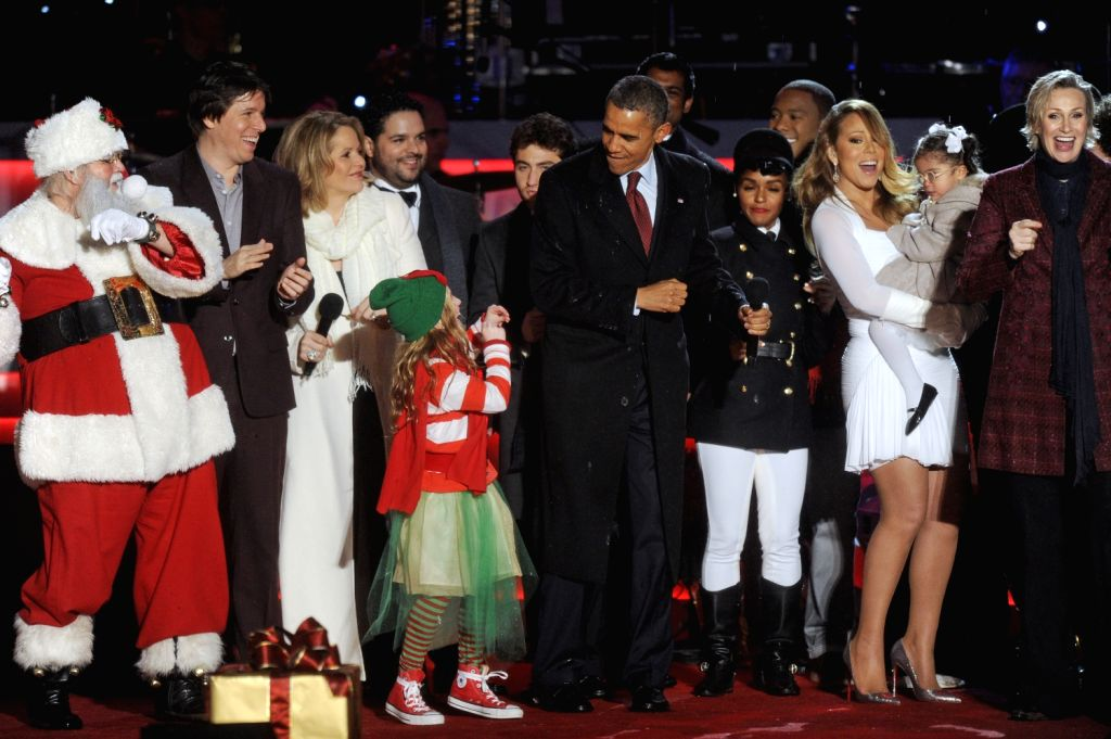 U.S. President Barack Obama (C) dangces with a girl during the 91st National Christmas Tree lighting ceremony on the Ellipse south of the White House in