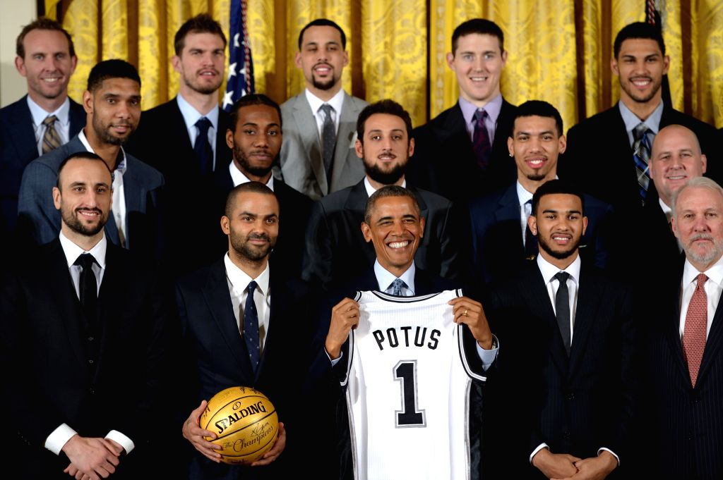 U.S. President Barack Obama (C) poses for group photos with members and coaches of San Antonio Spurs during an event honoring the 2014 NBA champions the San