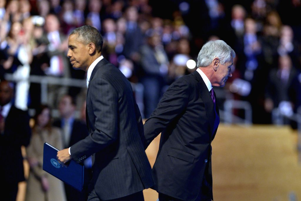 U.S. President Barack Obama (L) and outgoing U.S. Defense Secretary Chuck Hagel pass each other during a farewell ceremony at Virginia's Joint Base ...