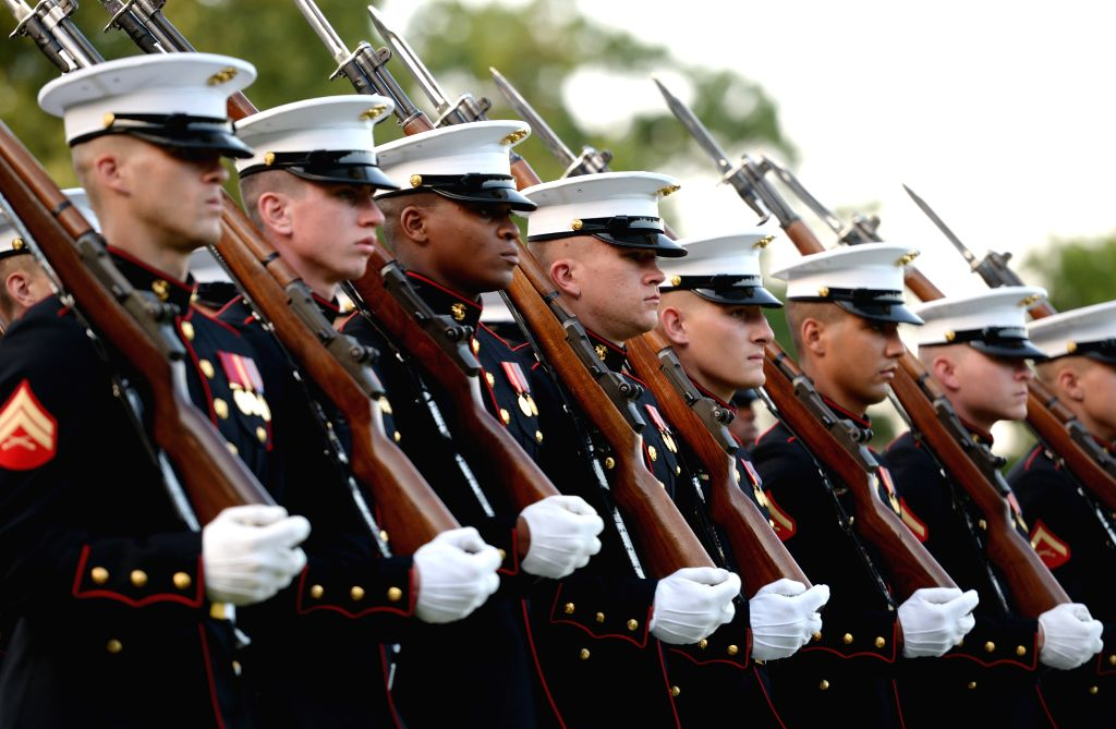 Members of the U.S. Marine Corps participate in the Marine Corps Sunset Parade at the Iwo Jima Memorial (formally known as the Marine Corps War Memorial) in