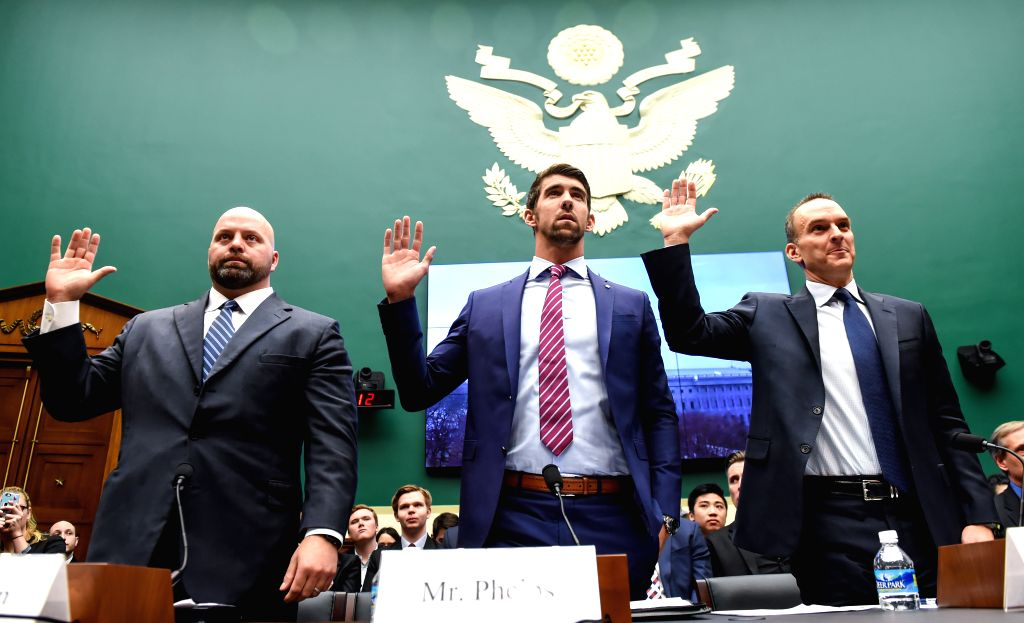 WASHINGTON D.C., March 1, 2017 - U.S. Olympic gold medalists Michael Phelps (C) and Adam Nelson (L) take an oath before testifying at the House Energy and Commerce Subcommittee on Oversight and ...