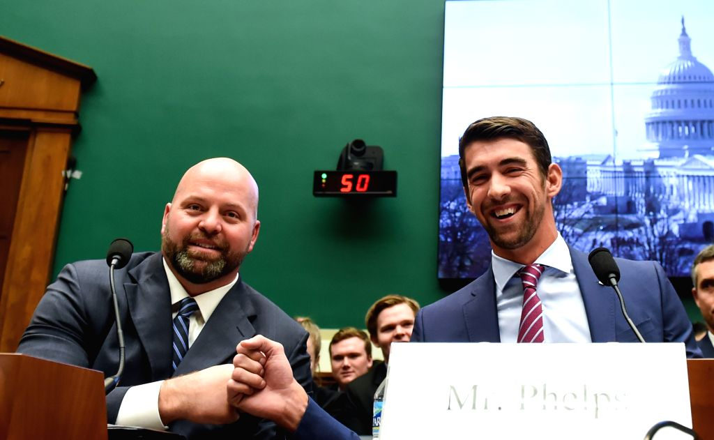 WASHINGTON D.C., March 1, 2017 - U.S. Olympic gold medalists Michael Phelps (R) and Adam Nelson fist-bump before they testify to the House Energy and Commerce Subcommittee on Oversight and ...