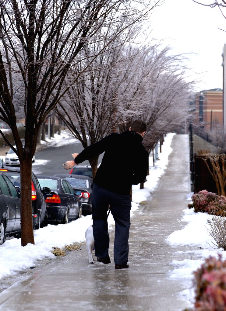 A man walks on an iced sidewalks in Arlington, Virginia, near Washington D.C., the United States, on March. 2, 2015. The federal government opened two-hour ...