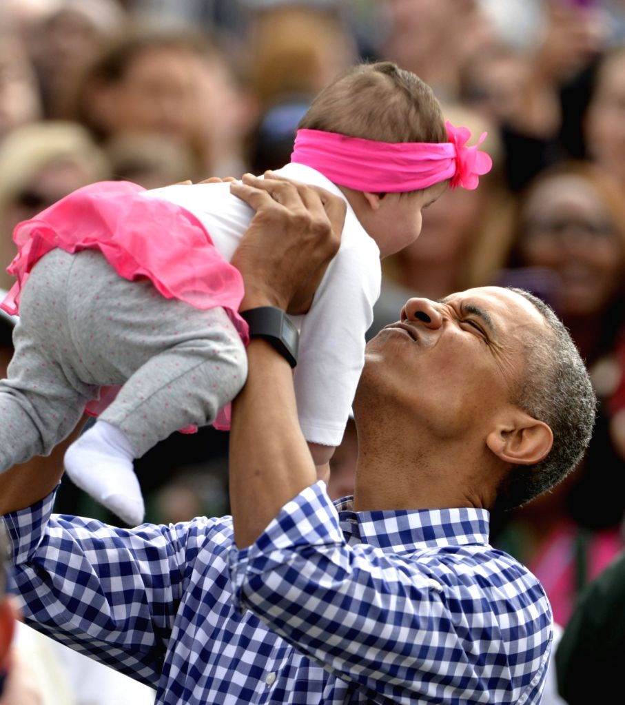WASHINGTON D.C., March 28, 2016 - U.S. President Barack Obama holds up a baby girl while attending the White House Easter Egg Roll at the White House in Washington D.C., the United States on March ...