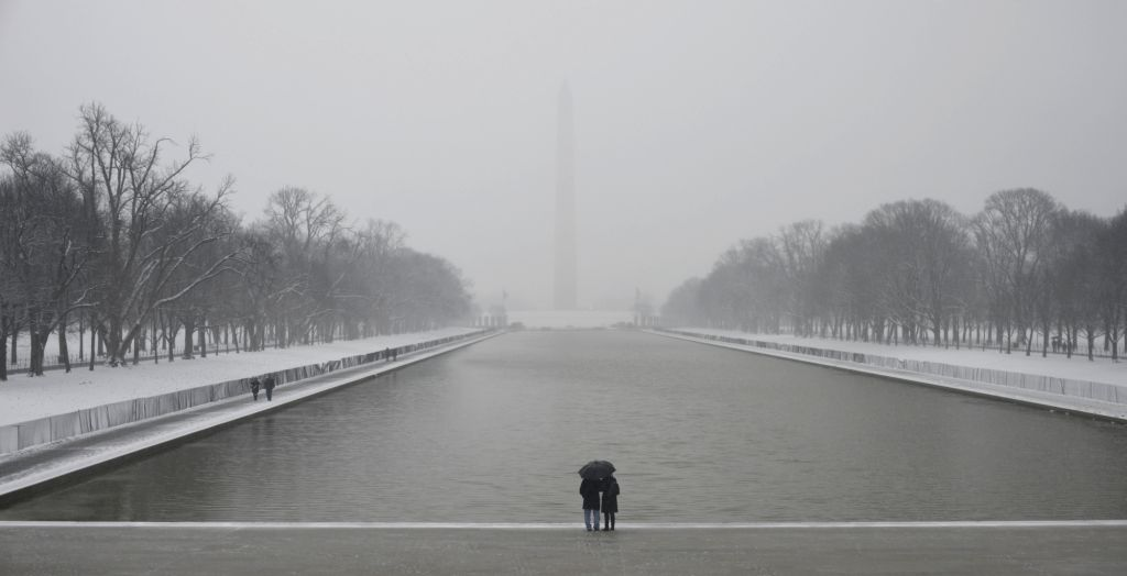 WASHINGTON, Feb. 20, 2019 - People stand in snow near the Lincoln Memorial Reflecting Pool in Washington D.C., the United States, on Feb. 20, 2019.