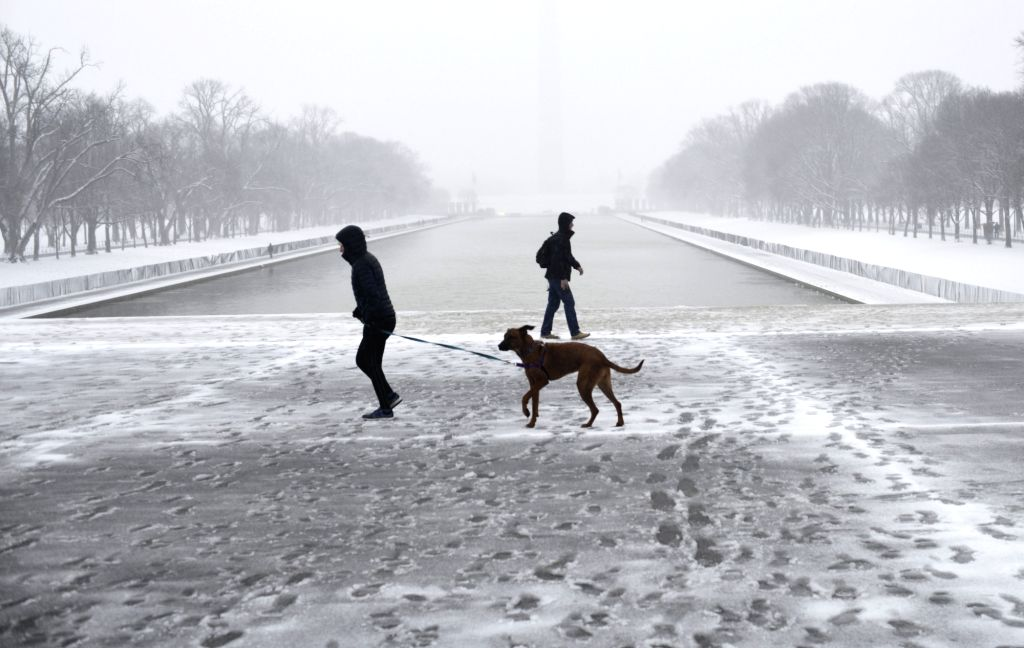 WASHINGTON, Feb. 20, 2019 - People walk in snow near the Lincoln Memorial Reflecting Pool in Washington D.C., the United States, on Feb. 20, 2019.