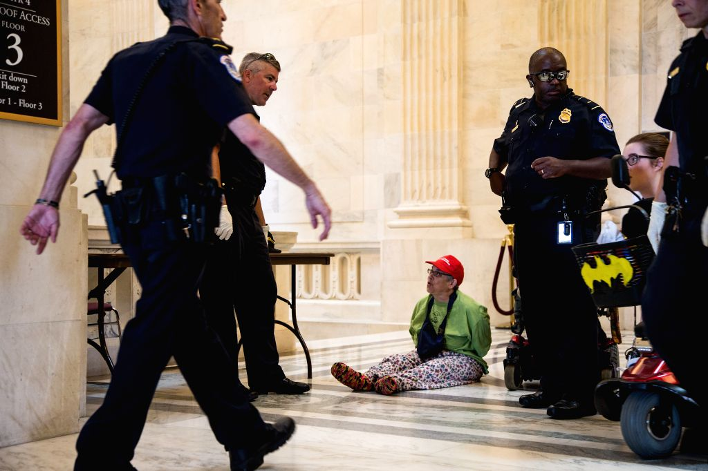 WASHINGTON, June 22, 2017 - A woman is detained during a protest inside the Russell Senate Office Building on Capitol Hill in Washington D.C., the United States, on June 22, 2017. Senate Republican ...