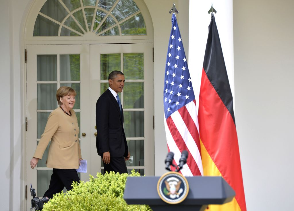 U.S. President Barack Obama (R) walks with with German Chancellor Angela Merkel for a joint news conference after their meeting at the Rose Garden of the White ...