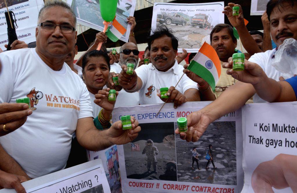 Watch Dog Foundation demanding permanent freedom from potholed roads in Mumbai on August 13, 2013. (Photo::: IANS)