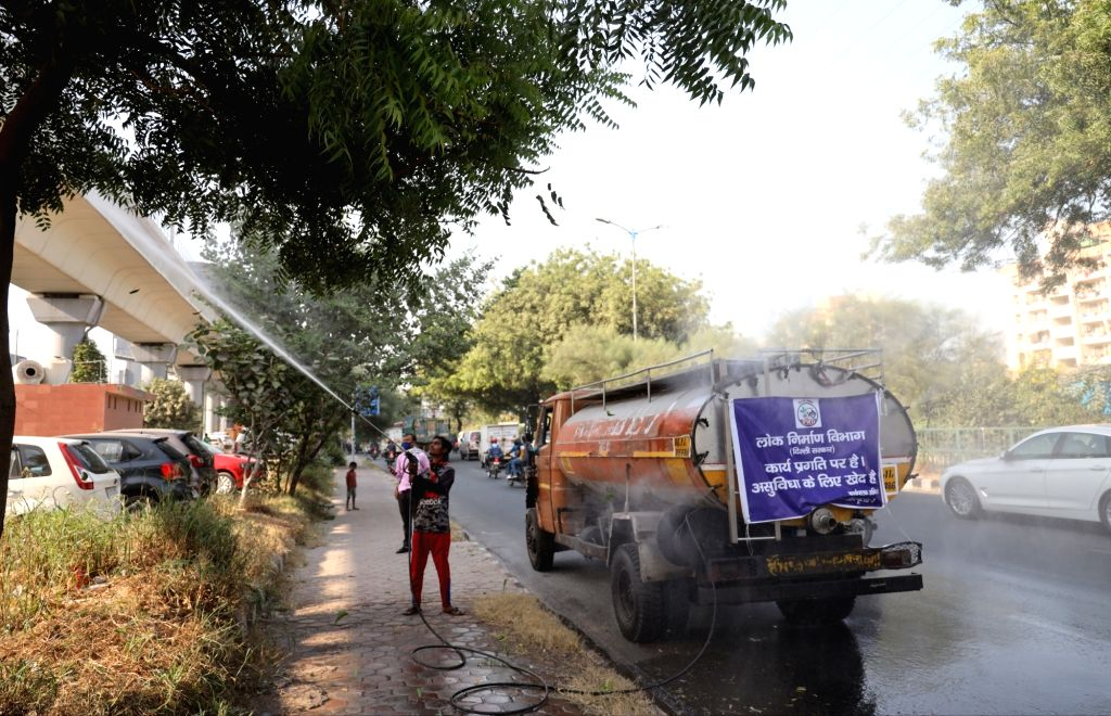 Water being sprinkled as a measure to reduce air pollution, at Sarita Vihar in New Delhi on Oct 21, 2020.