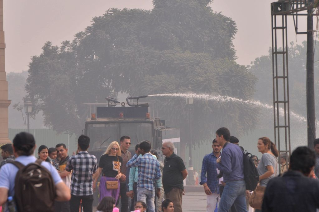 Water being sprinkled through a water tanker on a street at India Gate as a measure to curb pollution in New Delhi, on Nov 5, 2018.