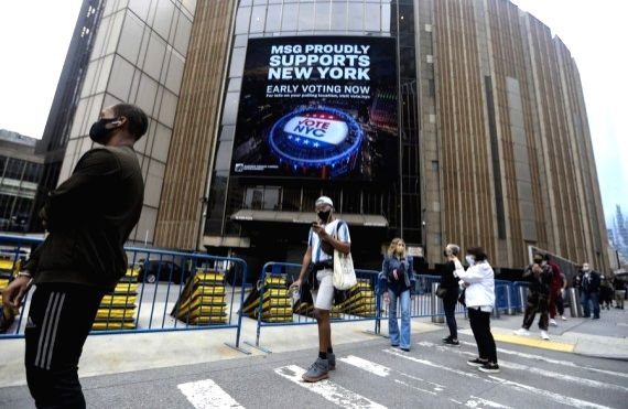 Wearing masks, voters line up with social distance to vote during the in-person early voting outside a polling station in Madison Square Garden in New York, the United States, Oct. 24, 2020. Early ...
