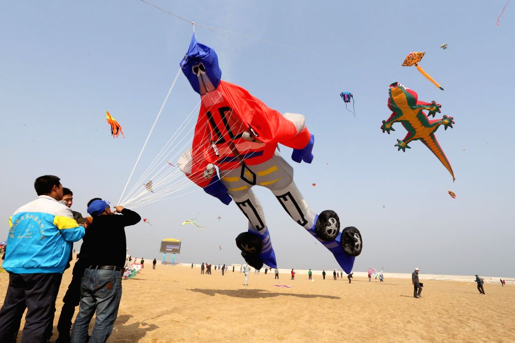 Participants fly kites during a kite fair held in Weifang, east China's Shandong Province, April 11, 2015. A total of 85 teams from all over the Weifang city took ...