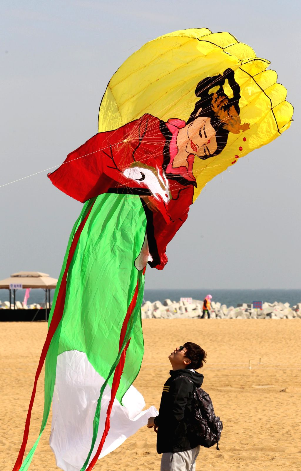 A man flies a dragon-head kite during a kite flying contest in Weifang,  east China's Shandong Province, April 16, 2014. Over 1,100 kites were flied on the event ..