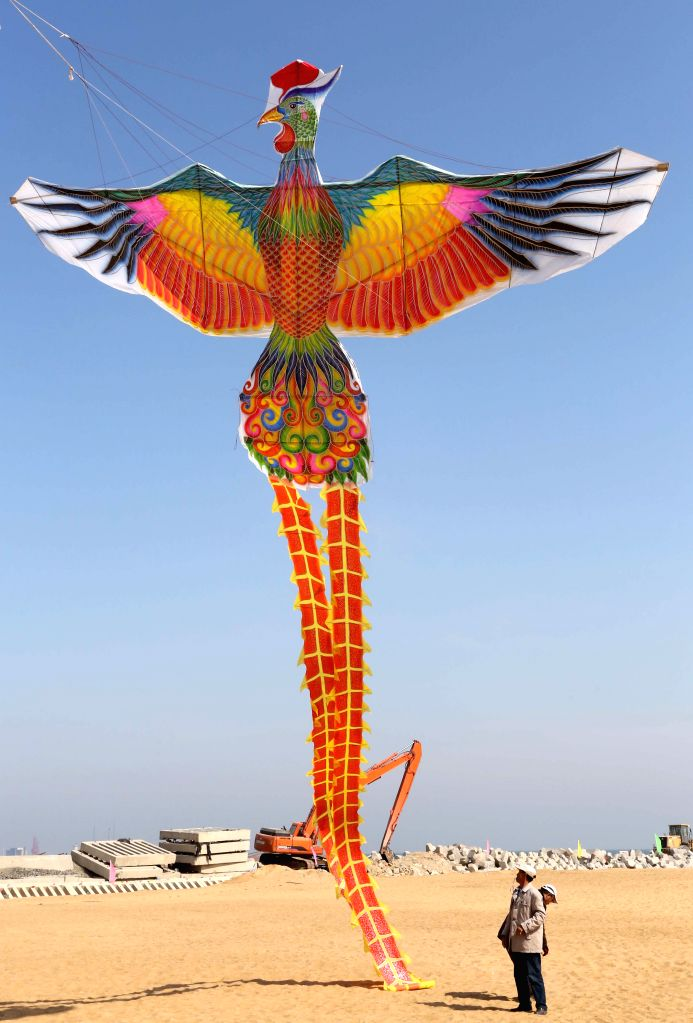 A man flies a phenix-shaped kite during a kite flying contest in Weifang,  east China's Shandong Province, April 16, 2014. Over 1,100 kites were flied on the event