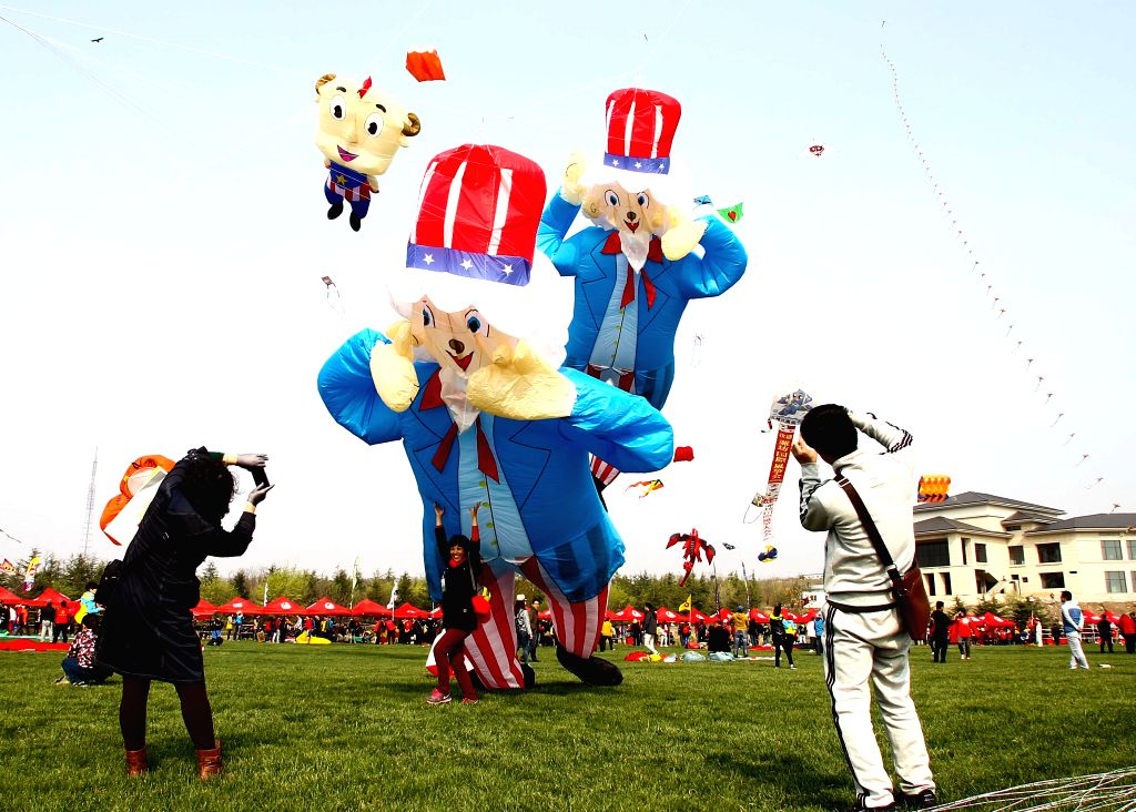Visitors take photos during a kite fair held in Weifang, east China's Shandong Province, April 18, 2015. Kites-flying fans from China and abroad took part in the ...