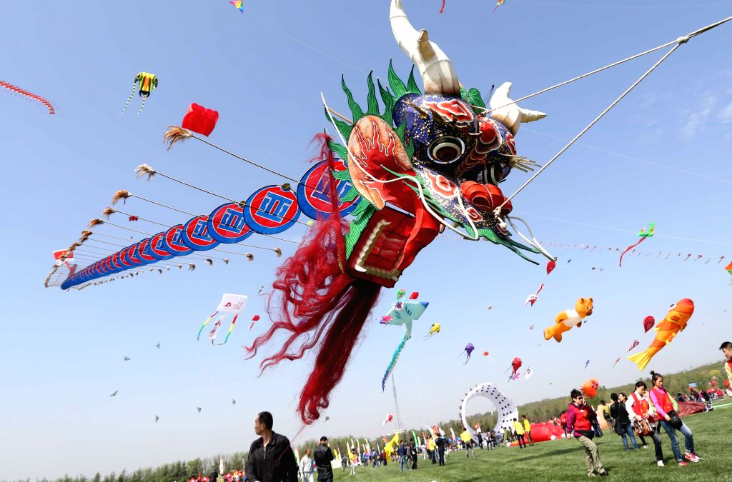 A dragon-shaped kite flies in sky during the 31th Weifang International Kite Festival in Weifang, east China's Shandong Province, April 19, 2014. (Xinhua/Zhang ...