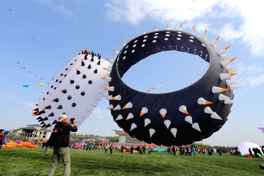Participants try to fly a kite during the 31st Weifang International Kite Festival in Weifang, east China's Shandong Province, April 19, 2014. (Xinhua/Zhang ...