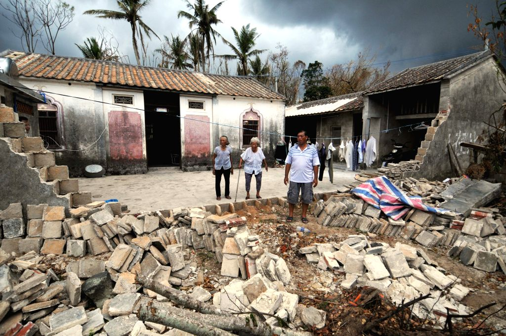 Zhang Yeping, a villager, stands in front of the ruins of his home, brought down by Typhoon Rammasun, in Shenlang Village under Wengtian Town of Wenchang, south ...