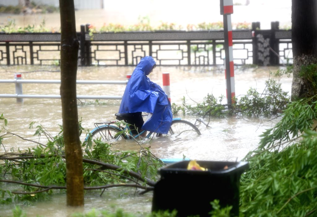 WENLING, Aug. 10, 2019 - A woman wades through a waterlogged street in Wenling, east China's Zhejiang Province, Aug. 10, 2019. China's National Meteorological Center issued an orange alert for ...