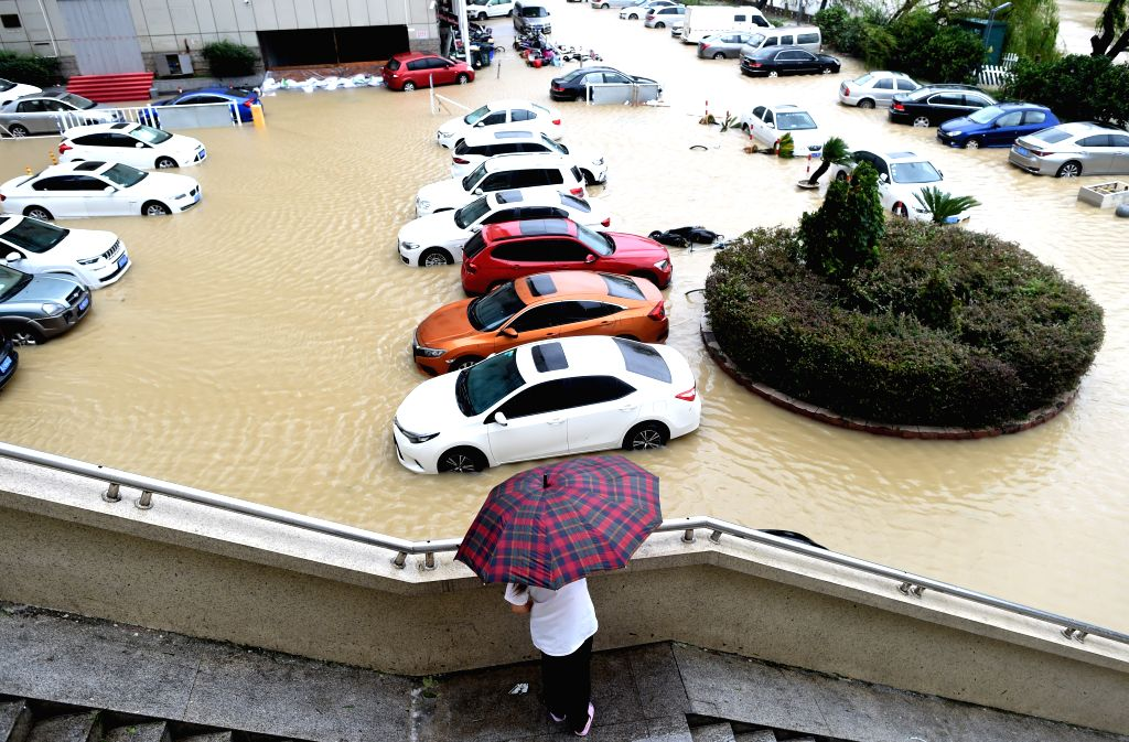 WENLING, Aug. 10, 2019 (Xinhua) -- Cars are stranded on a waterlogged parking lot in Wenling, east China's Zhejiang Province, Aug. 10, 2019. China's National Meteorological Center issued an orange alert for Typhoon Lekima on Saturday morning, as it l