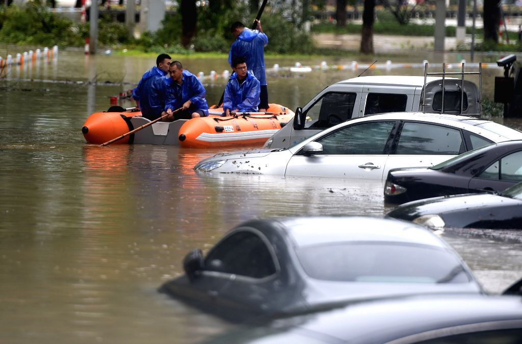 WENLING, Aug. 10, 2019 (Xinhua) -- People take a rubber dinghy while wading through a waterlogged street in Wenling, east China's Zhejiang Province, Aug. 10, 2019. At around 1:45 a.m., the center of Typhoon Lekima, the ninth typhoon of the year, made