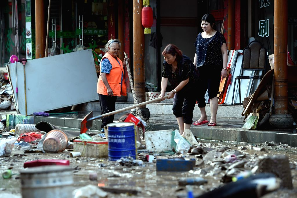 WENXIAN, July 12, 2018 - People clean up the rubbish after the flood in Bikou Town of Wenxian County, northwest China's Gansu Province, July 12, 2018. Water levels in the Yangtze River and the Yellow ...