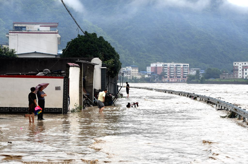 WENXIAN, July 12, 2018 - Villagers stand in flood water in Bikou Town of Wenxian County, northwest China's Gansu Province, July 12, 2018. Water levels in the Yangtze River and the Yellow River surged ...