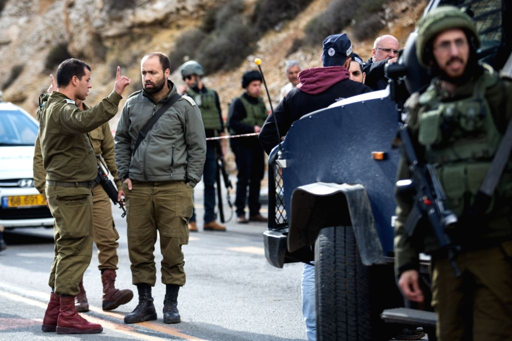 WEST BANK, Dec. 14, 2018 - Israeli forces inspect the site of a Palestinian drive-by shooting attack outside the West Bank settlement of Givat Asaf, northeast of Ramallah, on Dec. 13, 2018. Earlier ...