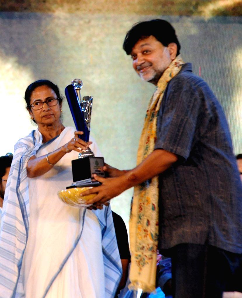 West Bengal Chief Minister Mamata Banerjee felicitates a Bengal artsite during a programme organised on the death anniversary of actor Uttam Kumar, in Kolkata on July 24, 2019. - Mamata Banerjee and Uttam Kumar