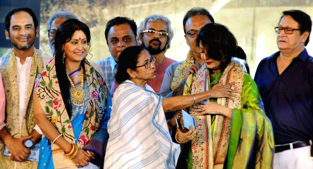 West Bengal Chief Minister Mamata Banerjee felicitates actress Satabdi Roy during a programme organised on the death anniversary of actor Uttam Kumar, in Kolkata on July 24, 2019. - Mamata Banerjee, Satabdi Roy and Uttam Kumar