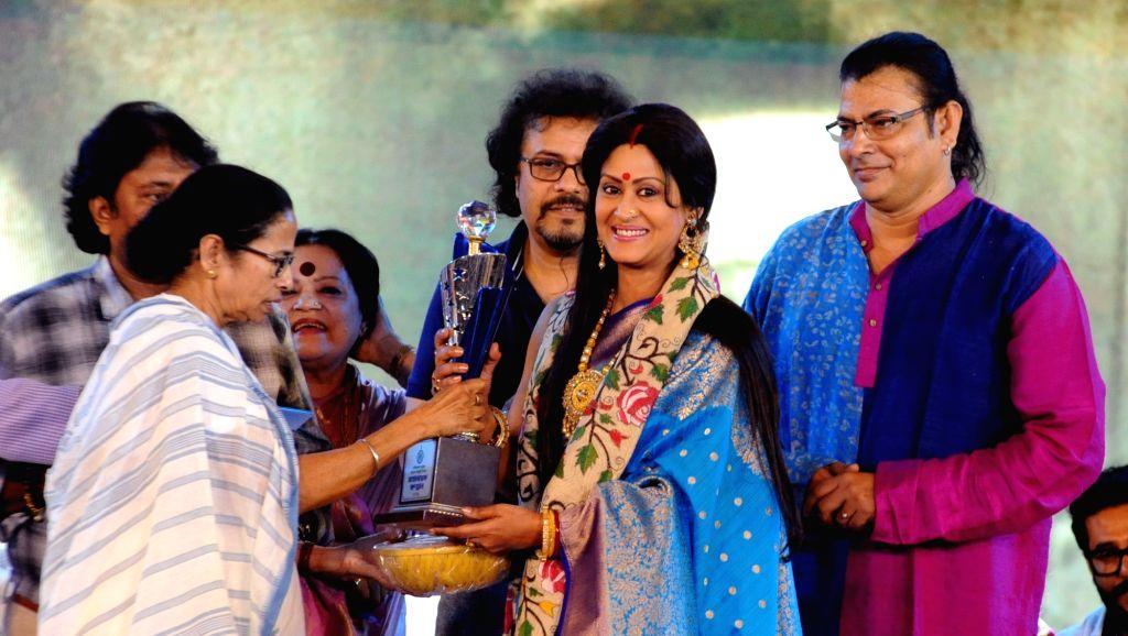 West Bengal Chief Minister Mamata Banerjee felicitates actress Indrani Halder during a programme organised on the death anniversary of actor Uttam Kumar, in Kolkata on July 24, 2019. - Mamata Banerjee and Uttam Kumar