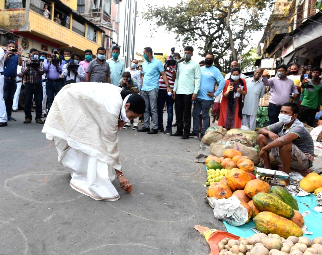 West Bengal Chief Minister Mamata Banerjee marks a street with chalk urging people to stringently follow social distancing on Day 2 of the 21-day nationwide lockdown imposed by the Narendra ... - Mamata Banerjee and Narendra Modi
