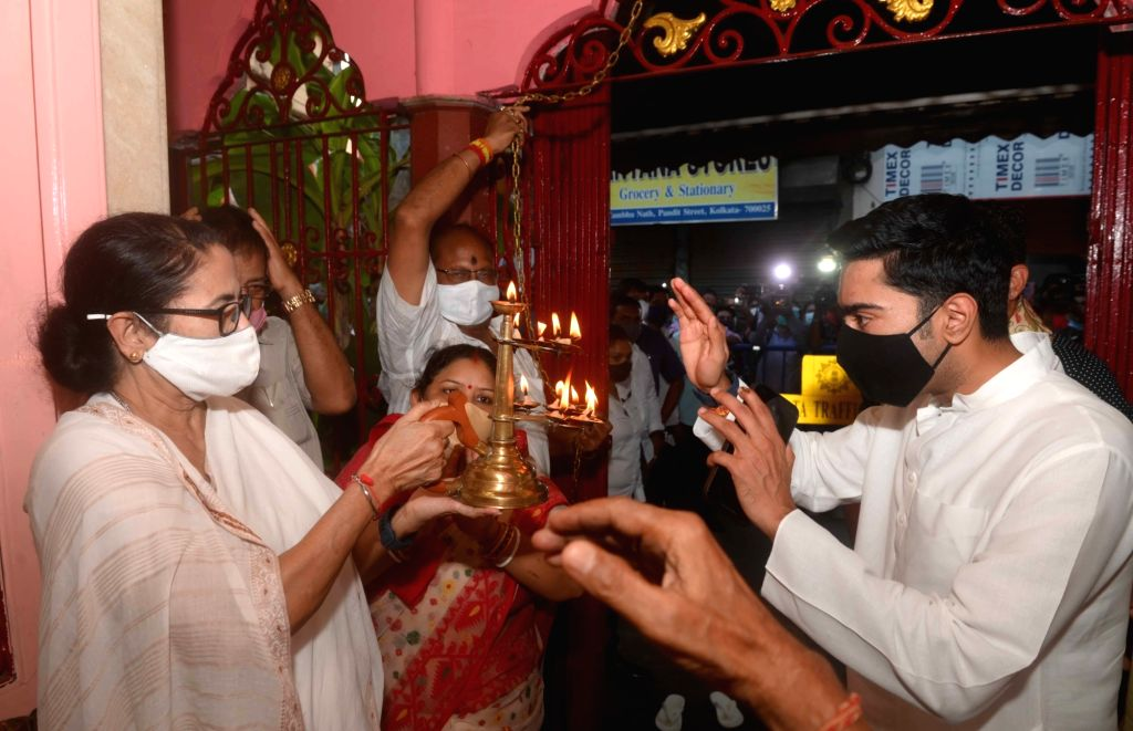 West Bengal Chief Minister Mamata Banerjee with her nephew and MP Abhishek Banerjee offers prayer at a Temple at Bhawanipur in Kolkata on Monday October 04 , 2021. - Mamata Banerjee and Abhishek Banerjee