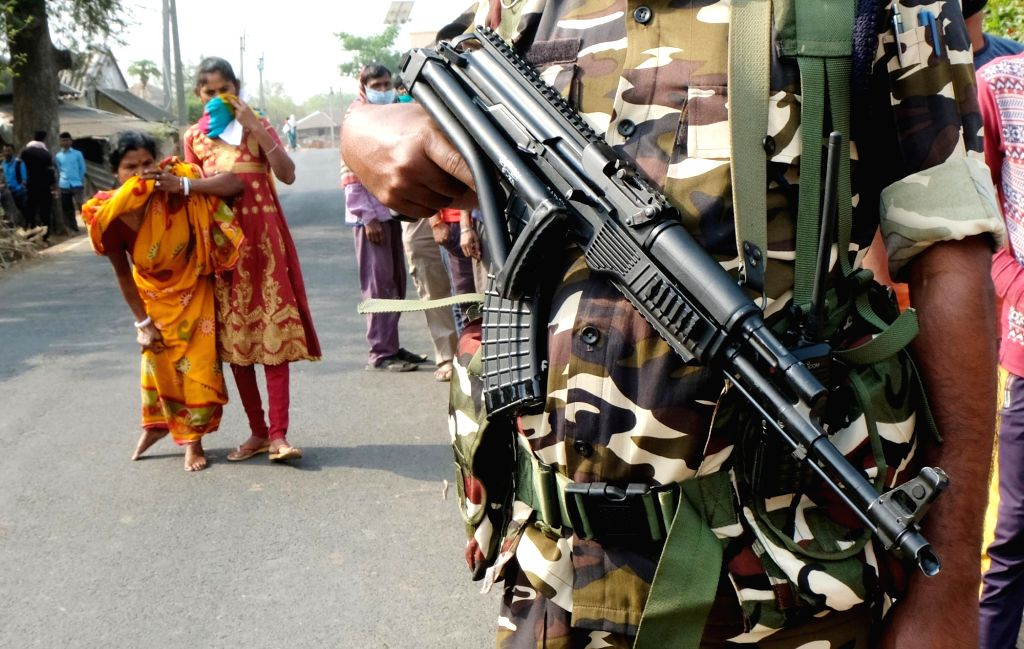 West Bengal: Physically challenged voter entering the polling centre under the shadow of automatic rifle  at Shirsha Primary School, Binpur of  Jhargram during the first phase of Assembly Election in ...