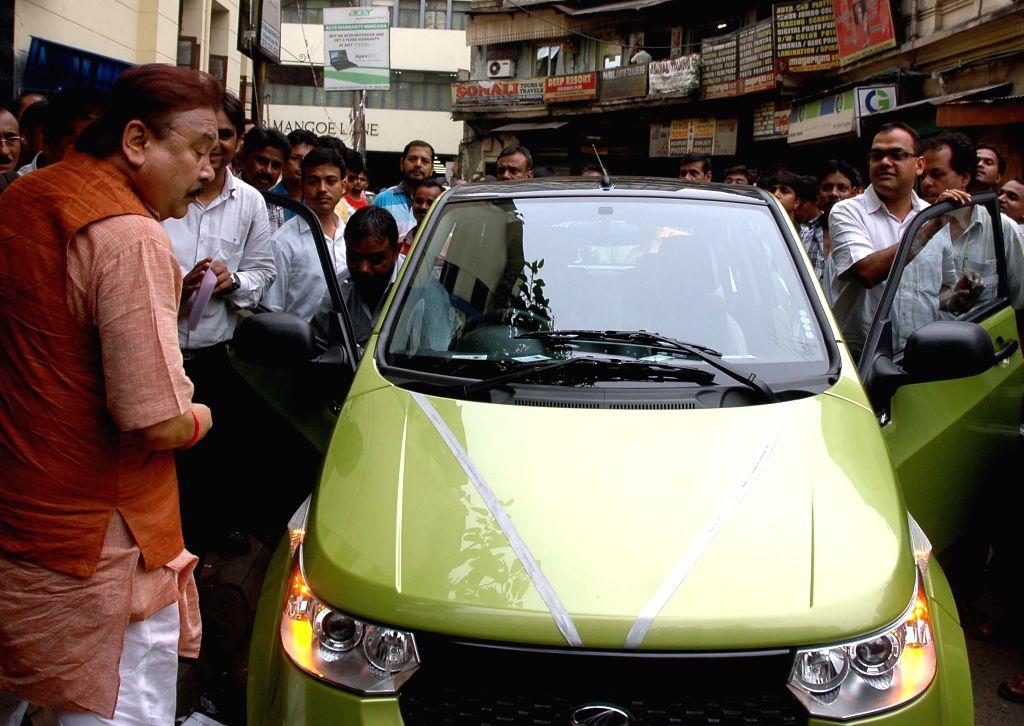 West Bengal Transport Minister Madan Mitra takes a look at Mahindra Reva E20 - an electric car in Kolkata on June 24, 2014.